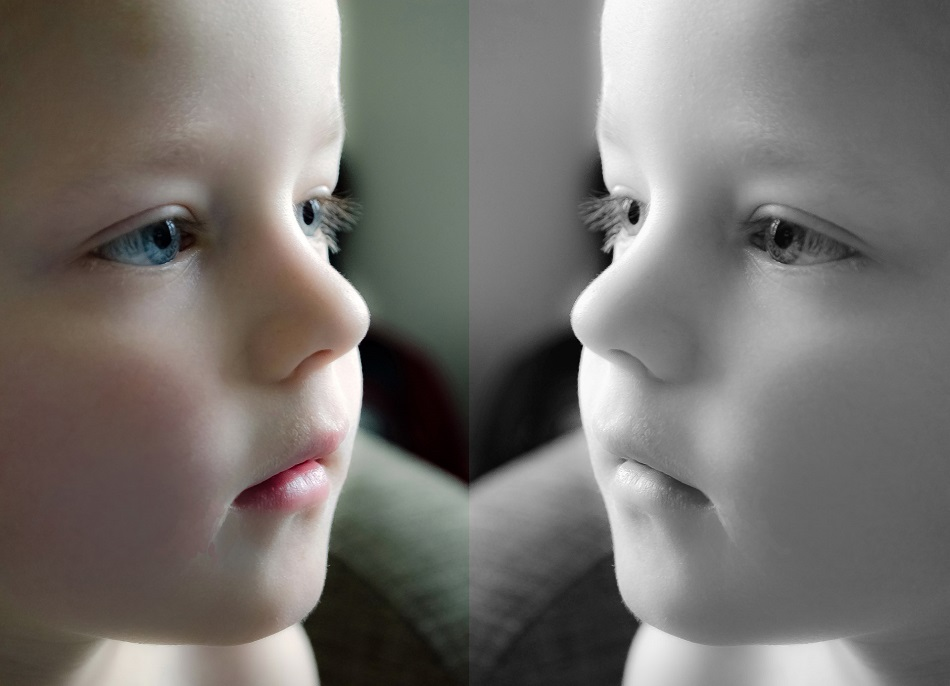 a child looks at a mirror image of themselves