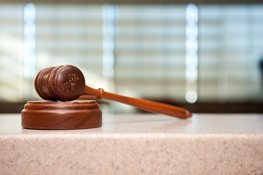 a gavel rests on its block on a counter
