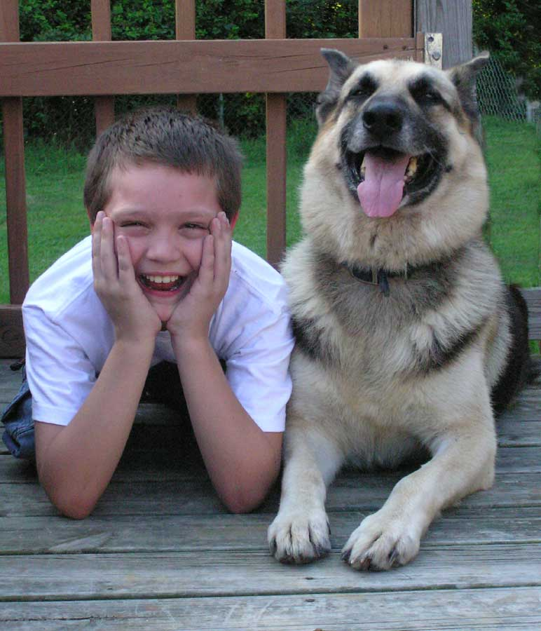a kid sits next to a dog, laughing