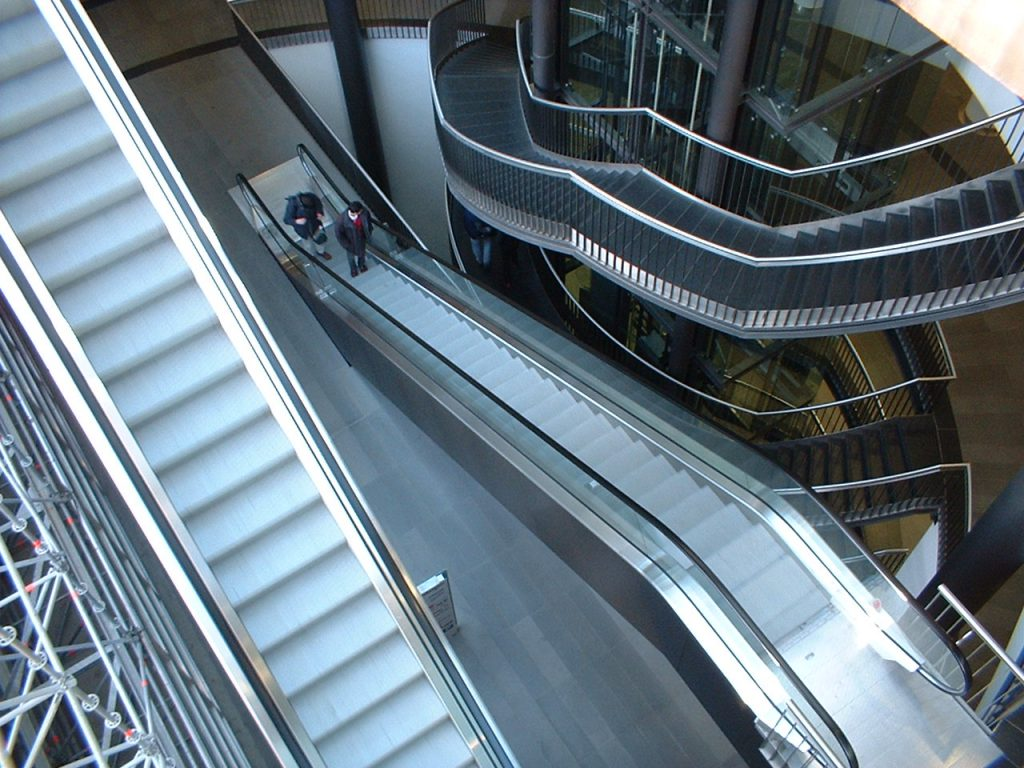 a downward view of multiple escalators and stairs