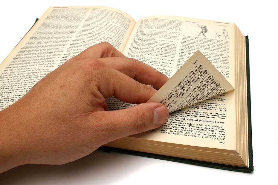 a hand peels back a page in a book