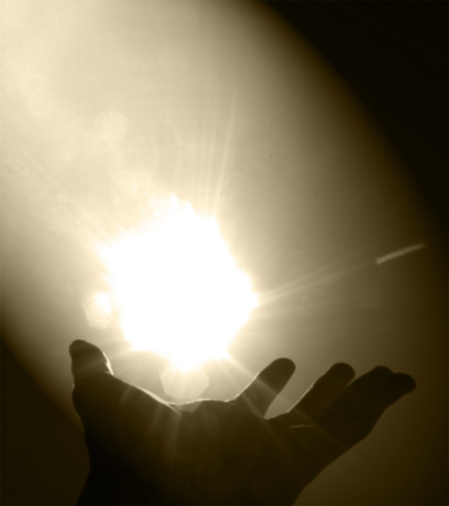 a hand reaches for a glowing ball of light