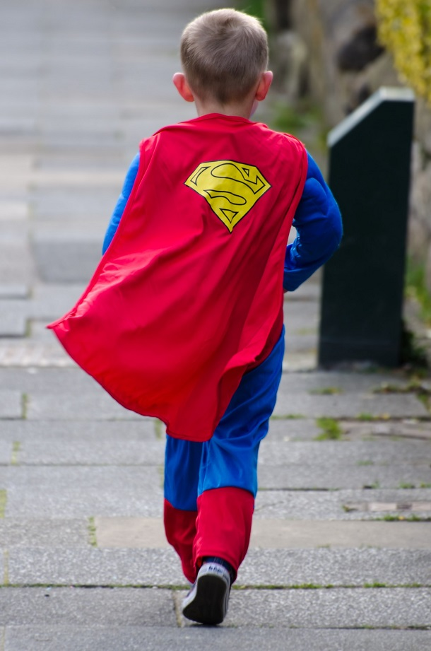 a child in a superhero costume walks down the street