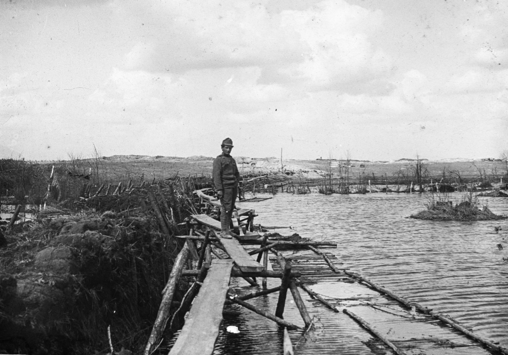 A man stands on a yet-to-be-completed bridge during the first world war