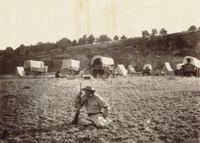 A man defends an encampment of covered wagons on the Oregon Trail