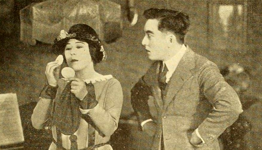 A man seemingly frustrated with a woman putting on make-up