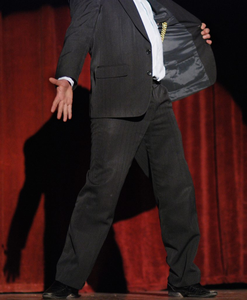 a man on a theatre stage in a suit addresses an audience