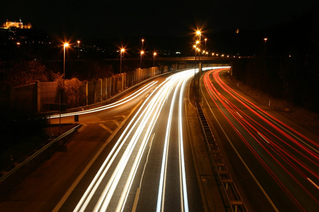 a time-elapsed photograph of car headlights going down a street. One pair deviates, leaving a gap in the stream