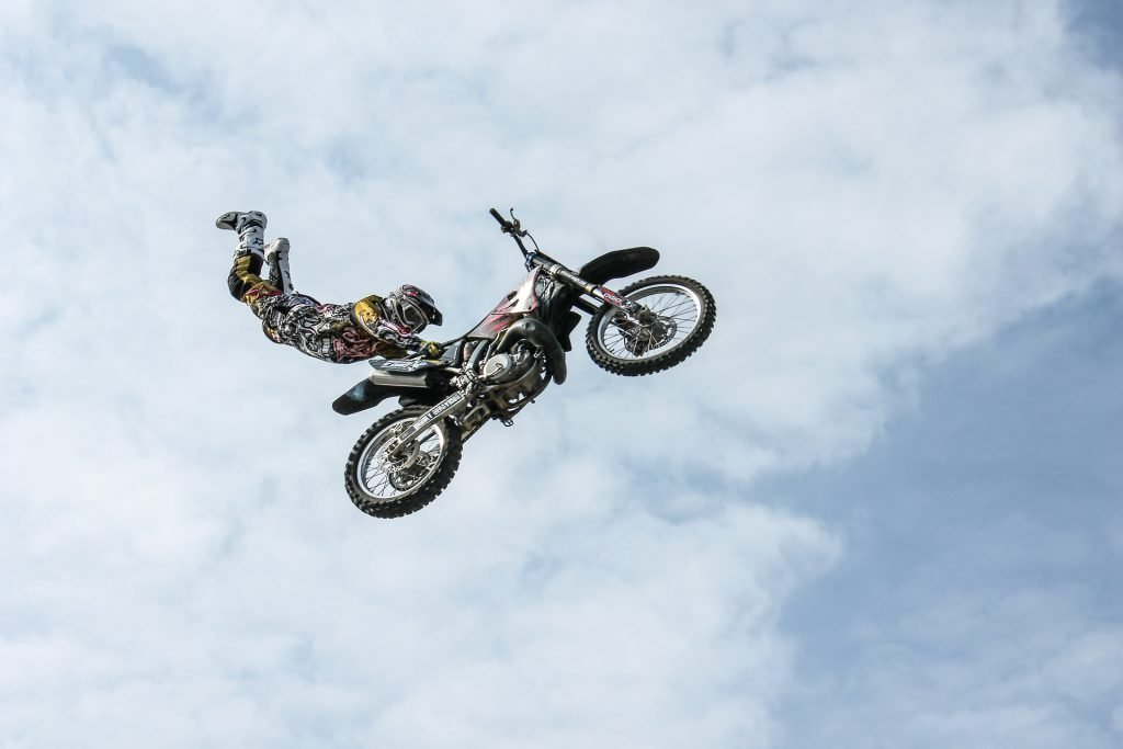 a motorcycle rider performs a stunt in midair