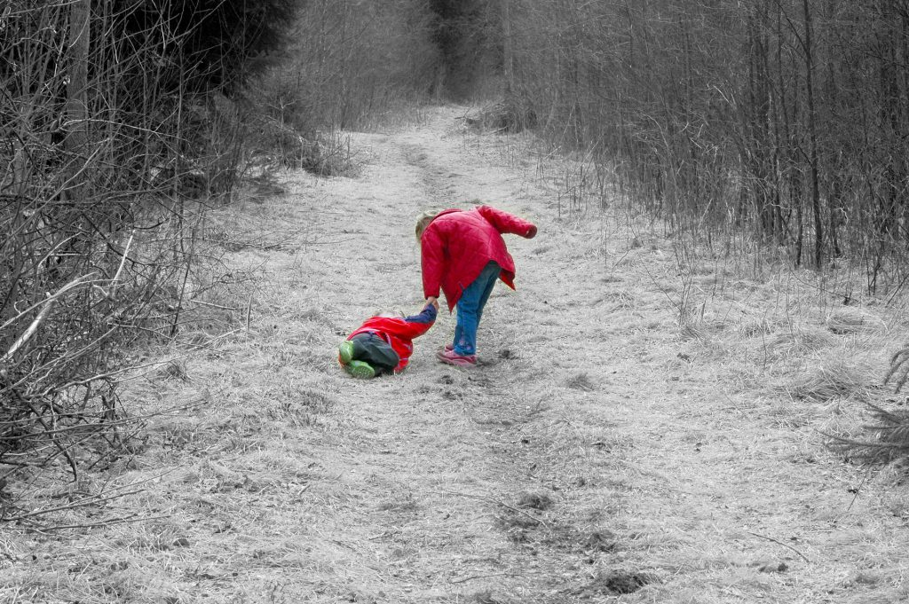 one child helps another child up in the middle of a snowy path