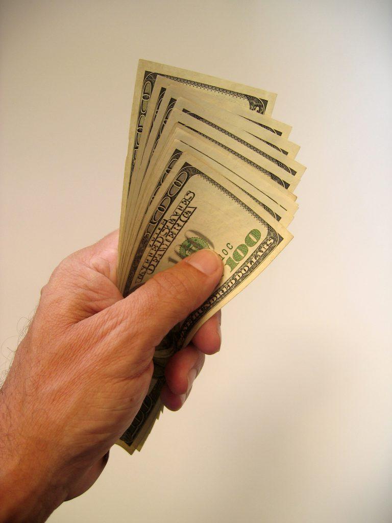 a hand holding several hundred dollar bills