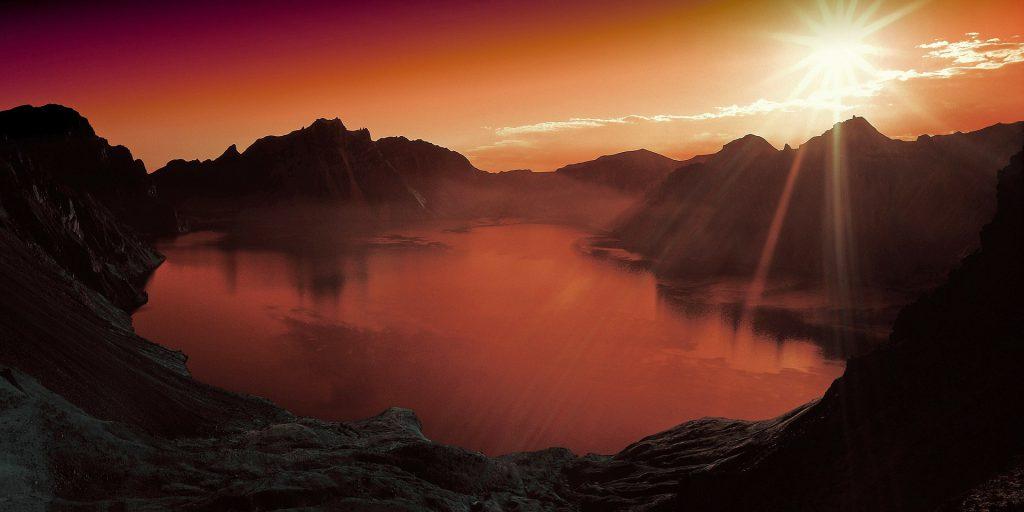 a sunset reflects on a foggy lake