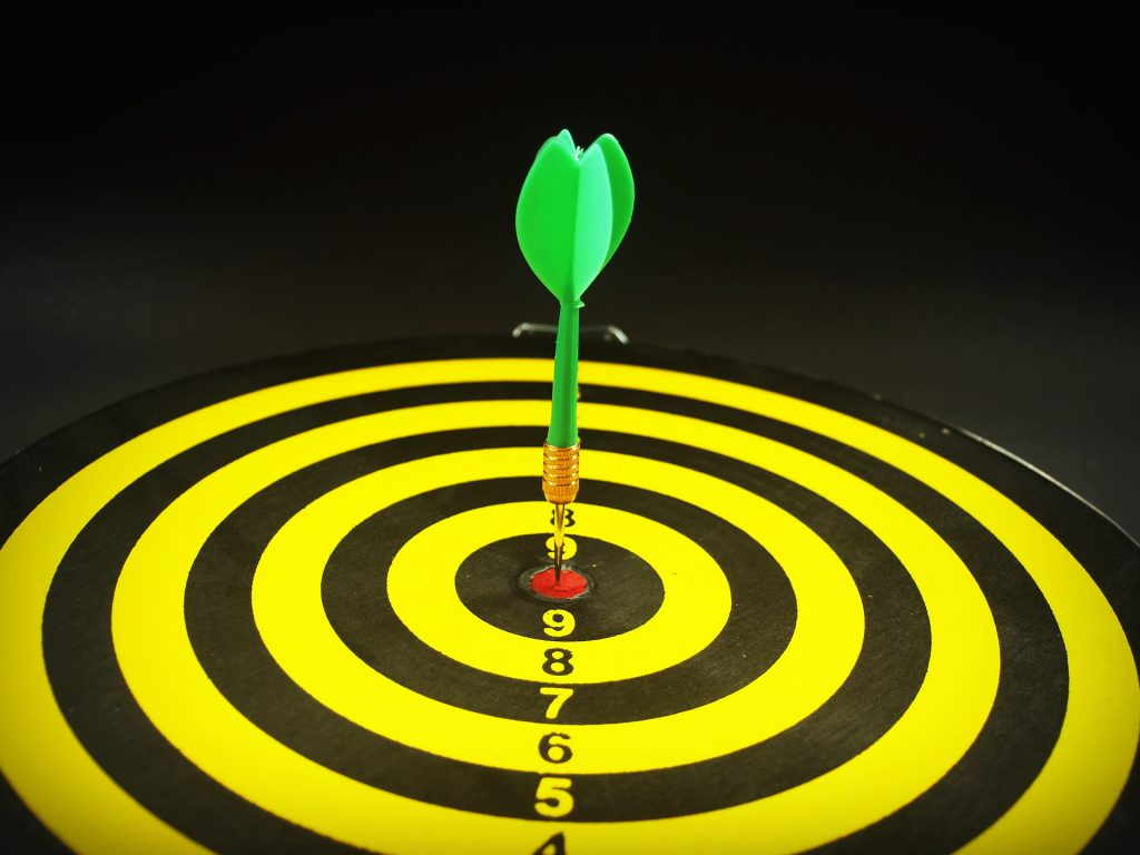 a dart rests in the center of a target's bullseye