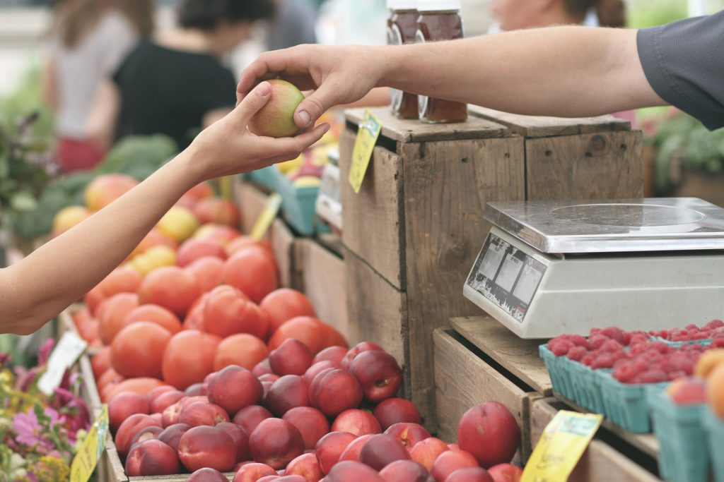 one person hands another person a fruit in a transaction at a fruit stand