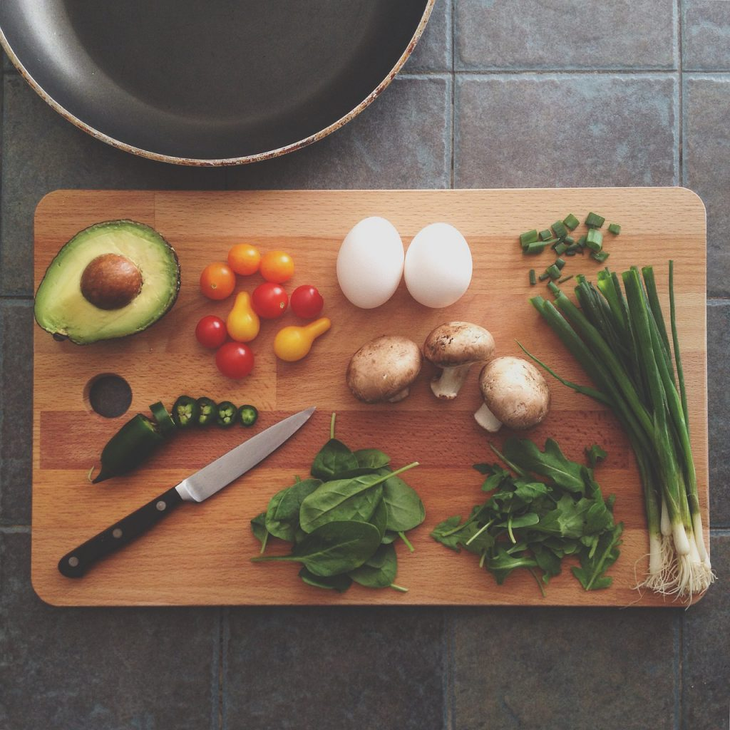 a cutting board with two neat rows of bowls containing ingredients for a dish