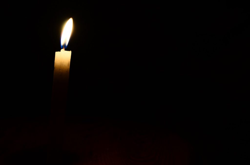 a lone candle is lit against a dark backdrop