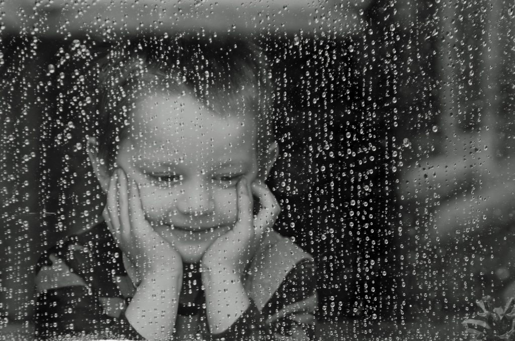 A child smiles while peering out a rain covered window