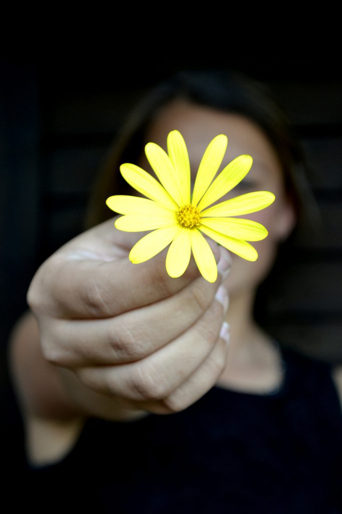 a woman holds out a flower as a gift