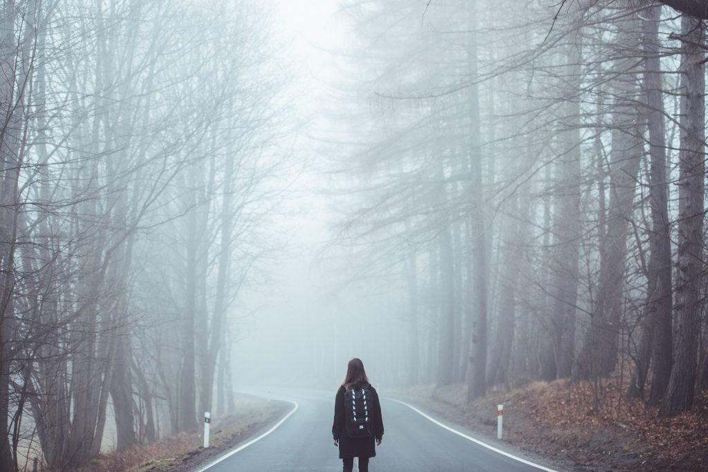 a woman approaches a foggy road looking unsure if she wants to travel it