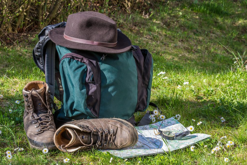 hiking gear which includes a backpack, shoes, hat, map and compass sits in the grass