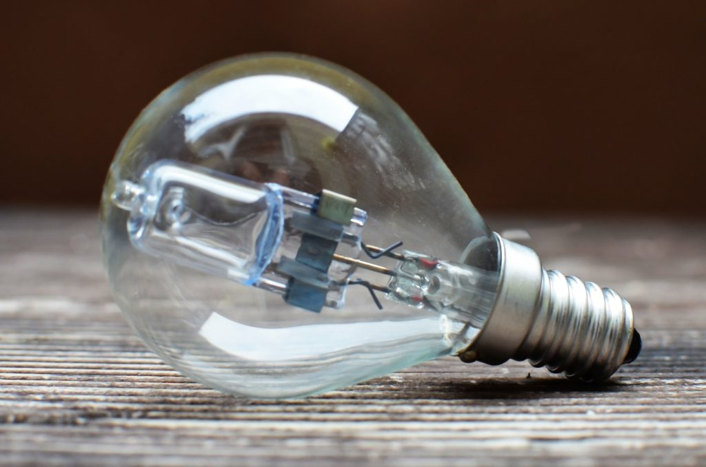 an unlit lightbulb rests on a wooden surface
