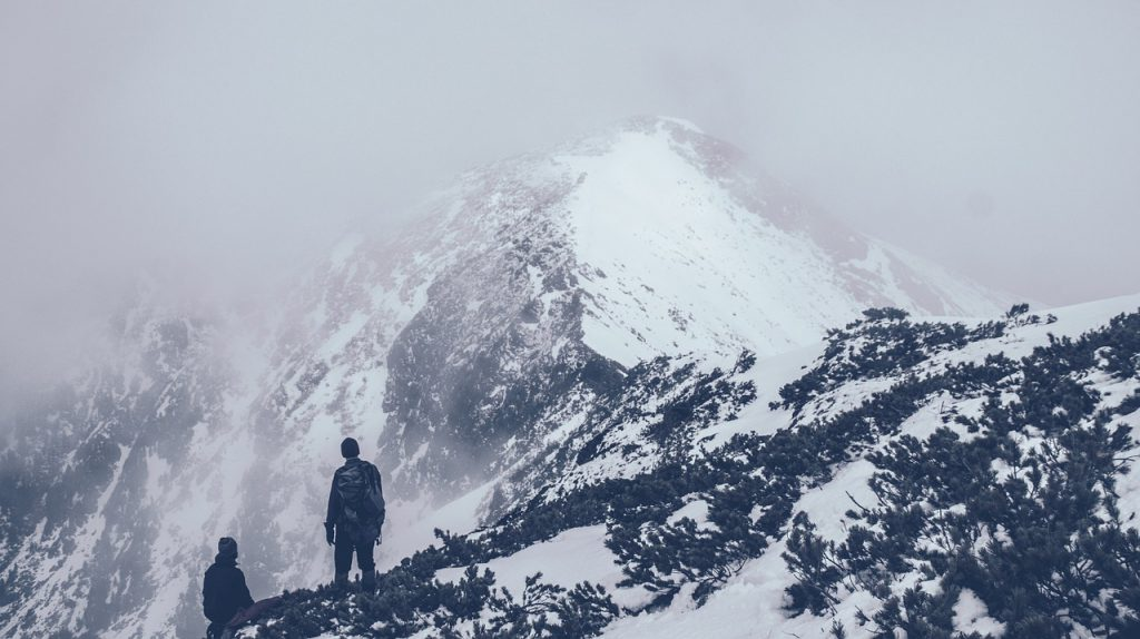two climbers stare at the peak of a mountain enveloped in cloud