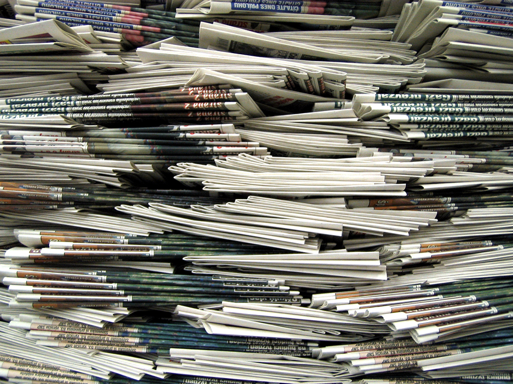 multiple stacks of newspapers piled on top of each-other