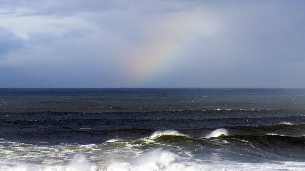 a faint rainbow appears at the horizon of a deep blue ocean