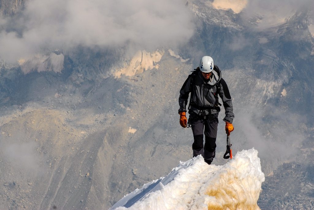 a man climbs to the top of a summit, smiling, with his tools in hand