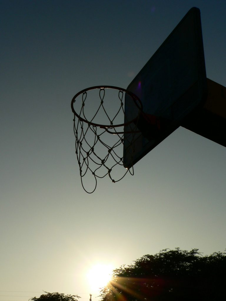 a basketball hoop looms overhead backlit by the sunset