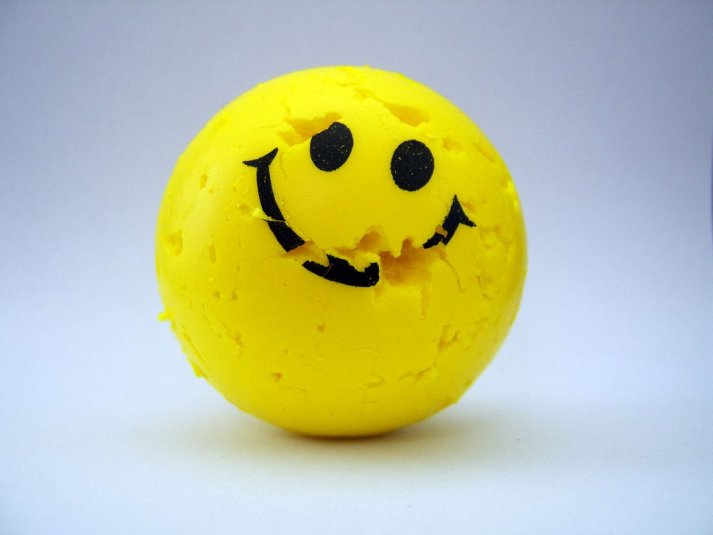 a smiley face ball with many pieces missing but you can still see the smile