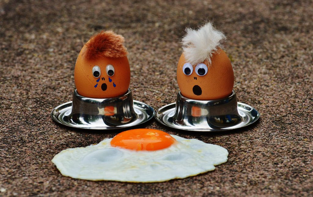 two whole eggs with painted on faces look on in shock at a fried egg on the ground
