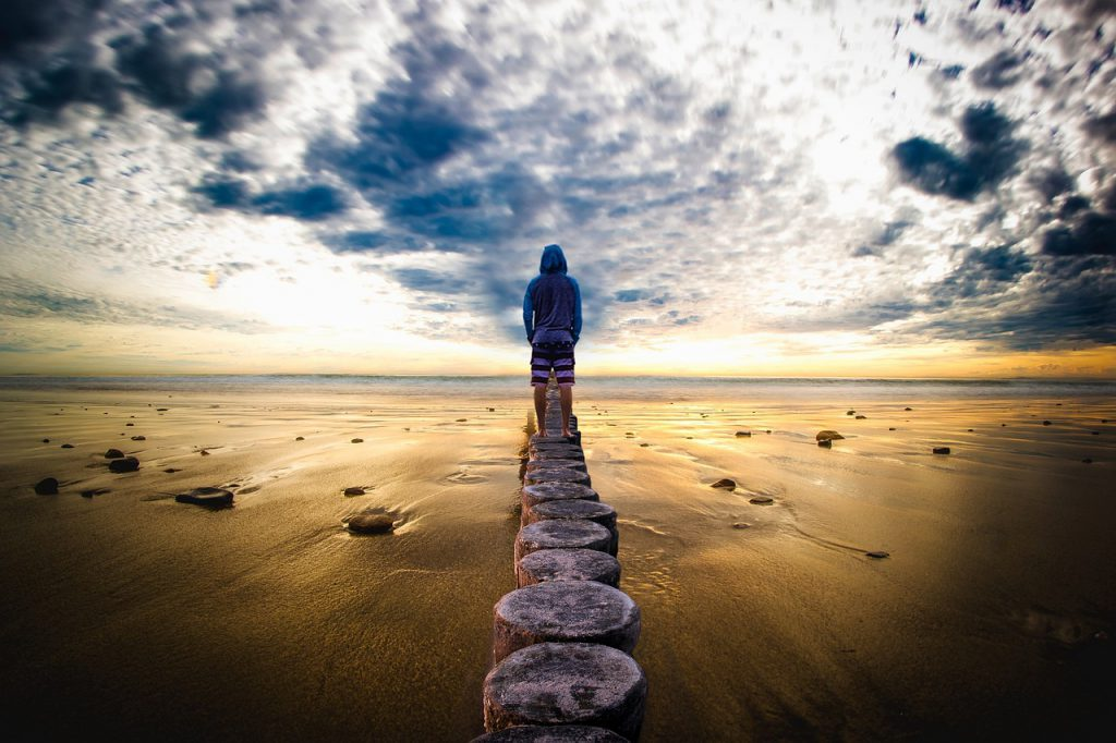 a girl walks out towards the ocean on a row of stumps