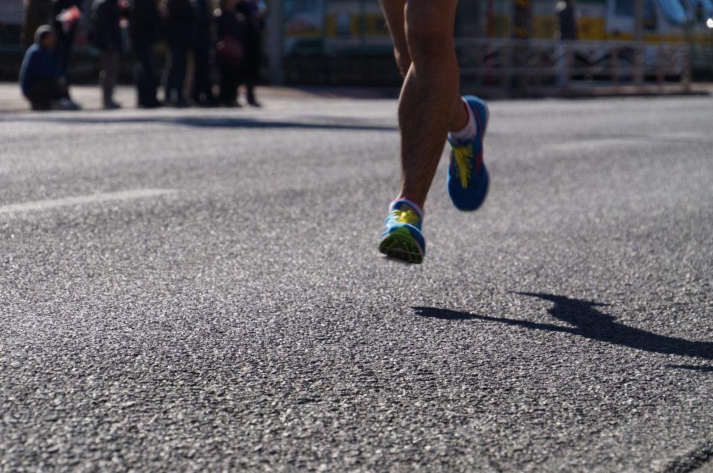 view of sneakered feet running down a road in the sunshine