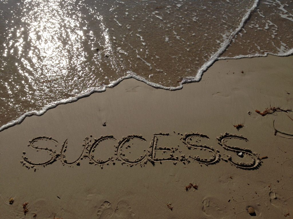 the word success written in the sand is seconds away from being washed away by the tide