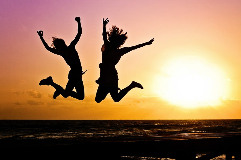 two friends leap into the air on a beach