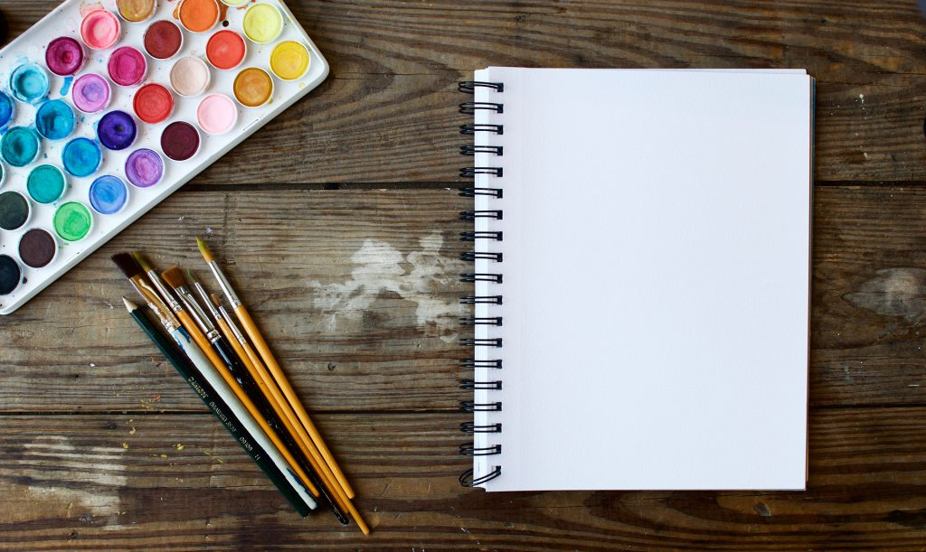 a blank canvas sits next to a painting set