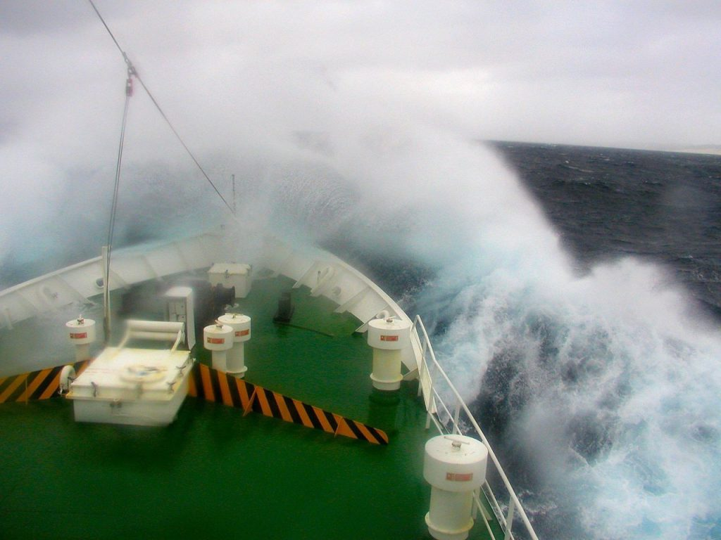 a large wave crashes over the bow of a ship