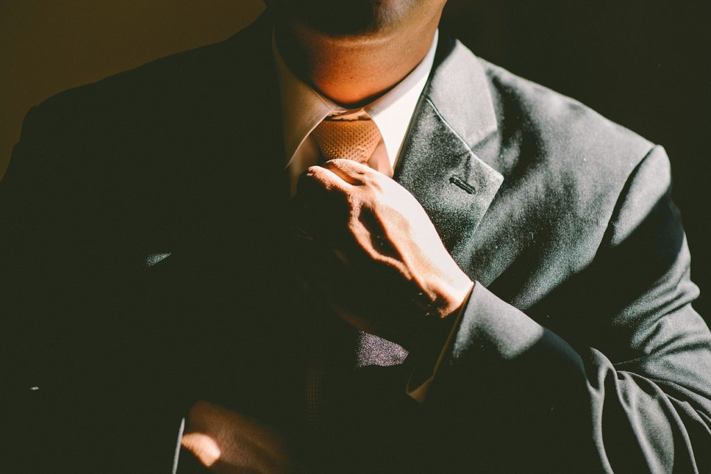 a man in a suit tightens up his necktie