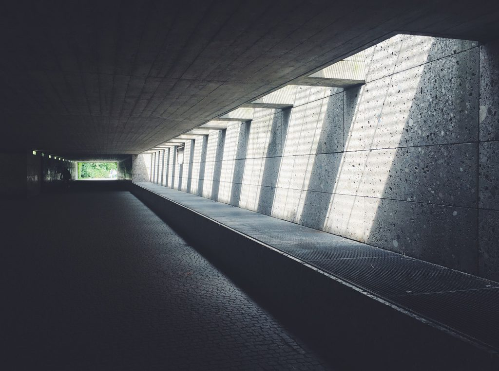a tunnel with sunlight beaming down in intervals