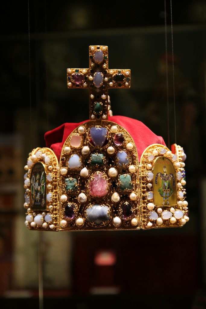 a crown with decorative stones on it sits in a display case