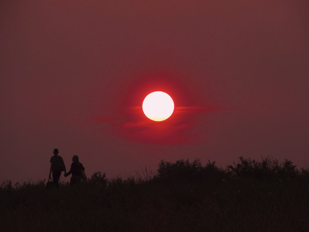 two people walk in the sunset holding hands