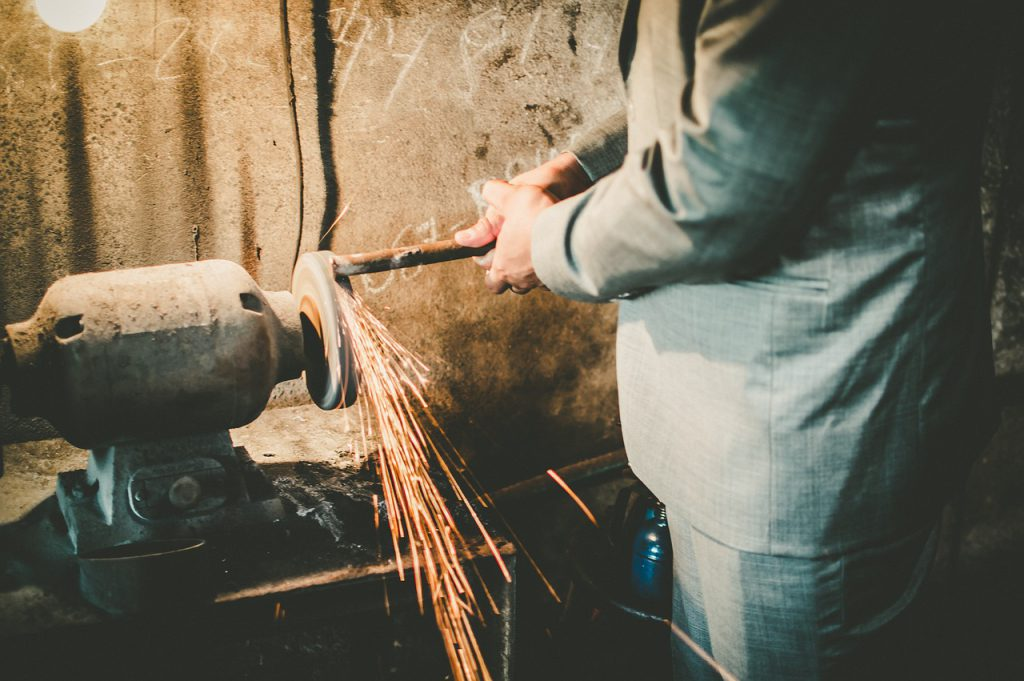 a man in a suit grinding a piece of metal on a wheel