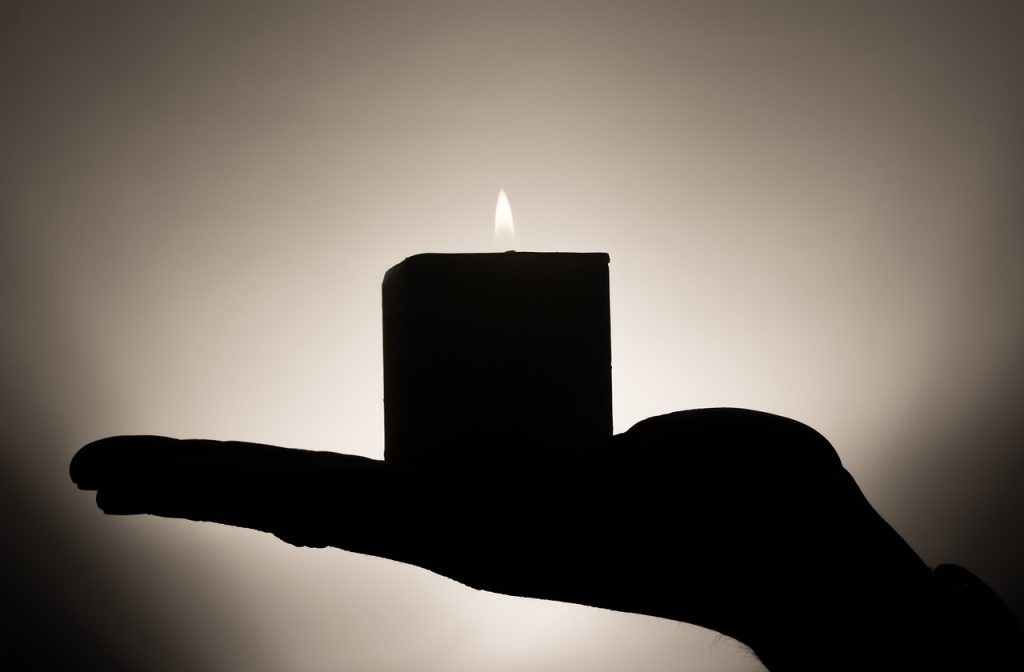a hand holding up a candle