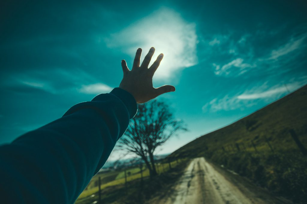 a hand reaching for the sun against a blurry landscape