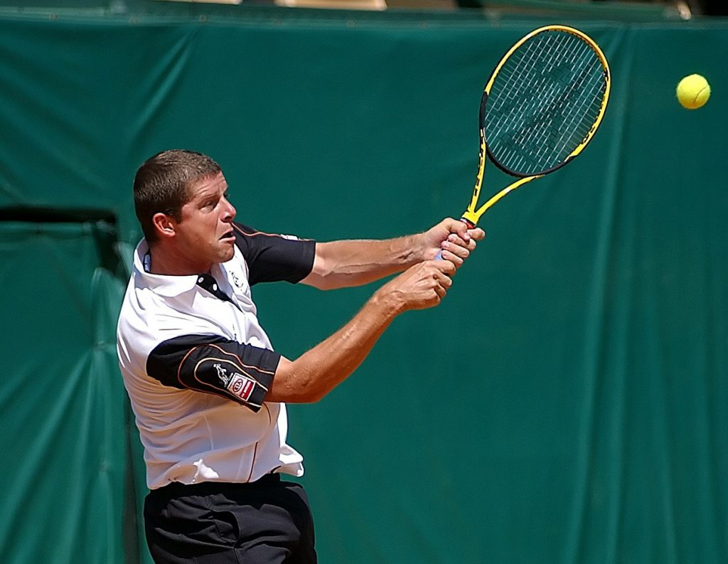 a man swinging a tennis racket as the ball comes towards him