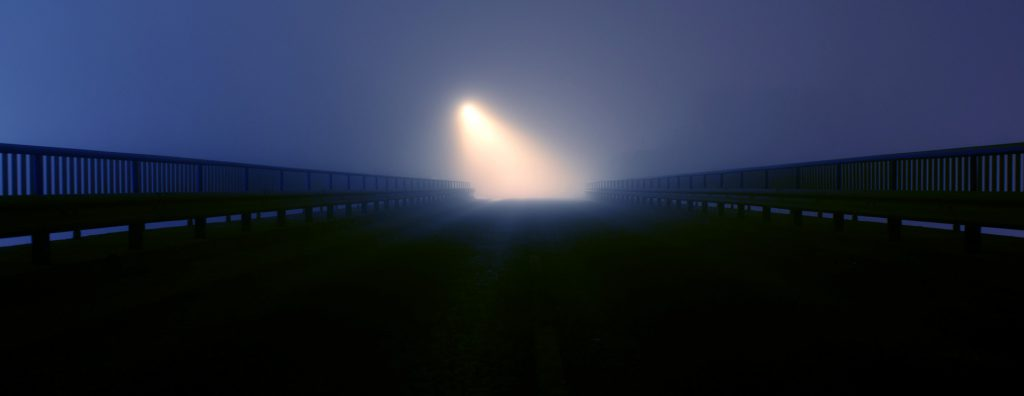 a light appears in the distance in a thick fog