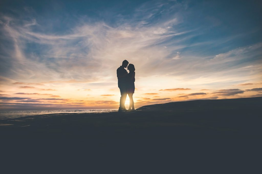 a couple embraces on a beach at sunset