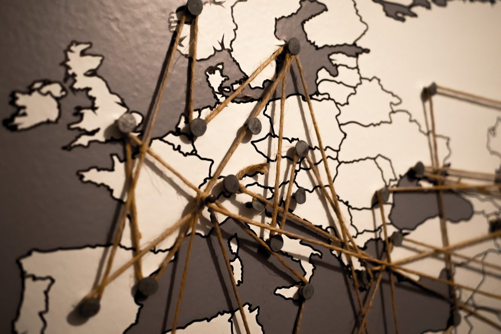 twine and nails strung across a world map, marking connections