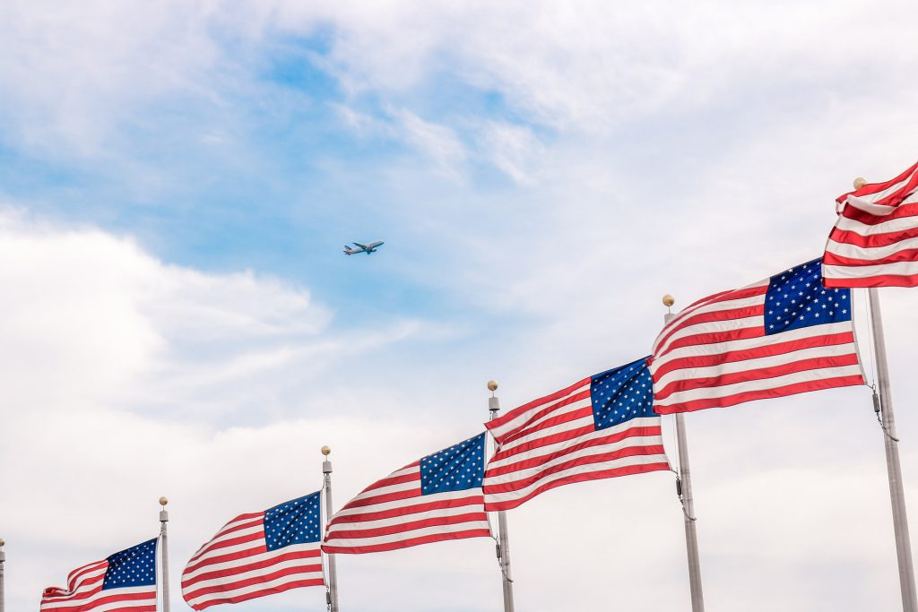 a row of flags and an airplane against the sky